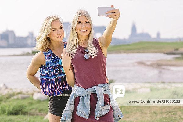 Zwei lächelnde junge Frauen  die einen Selfie am Flussufer nehmen.