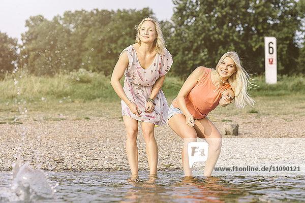 Zwei junge Frauen überspringen Steine im Fluss