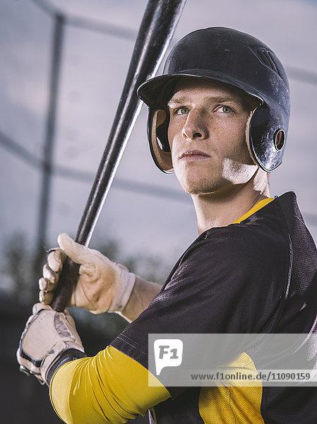 Baseballspieler hält Schläger