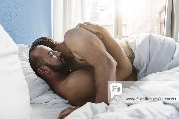 Schwules Paar umarmt sich im Bett