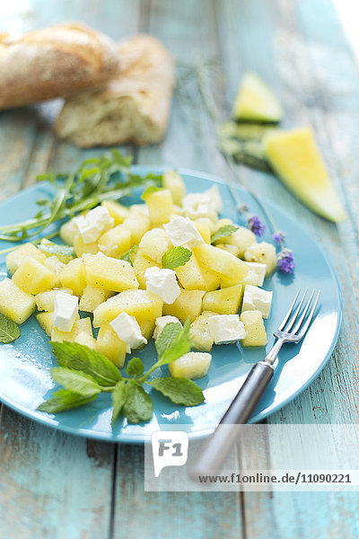 Melonensalat  gelbe Wassermelone  Feta  Minze und Rucola auf dem Teller Melonensalat, gelbe Wassermelone, Feta, Minze und Rucola auf dem Teller