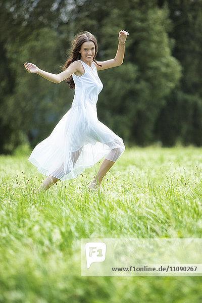 Glückliche Frau in weißem Sommerkleid auf einer Wiese