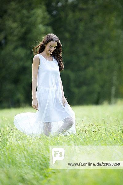 Fröhliche Frau in weißem Sommerkleid auf einer Wiese unterwegs