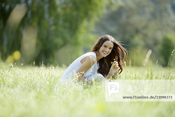 Happy woman crouching on a meadow picking flowers