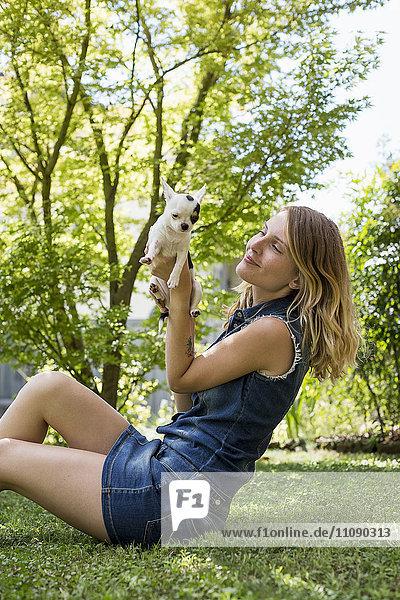 Glückliche Frau sitzt mit ihrem Chihuahua auf einer Wiese im Garten.
