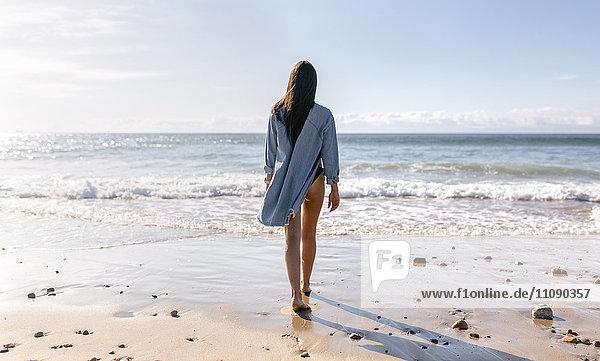 Spanien  Asturien  schöne junge Frau am Strand  Rückansicht