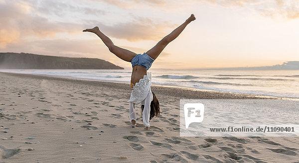Spanien  Asturien  schöne junge Frau am Strand  die Räder dreht