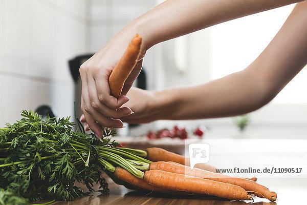 Frau entfernt Blätter von Karottenbüscheln