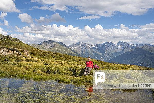 Frau beim Wandern in den Alpen  Rast am See