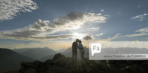 Ein glückliches Paar küsst sich bei Sonnenuntergang in den Bergen.