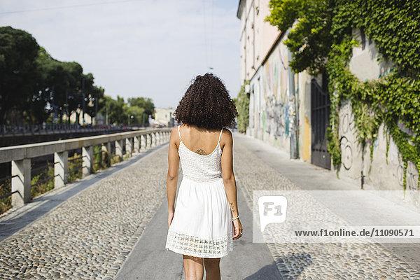 Rückansicht der gehenden jungen Frau in weißem Sommerkleid