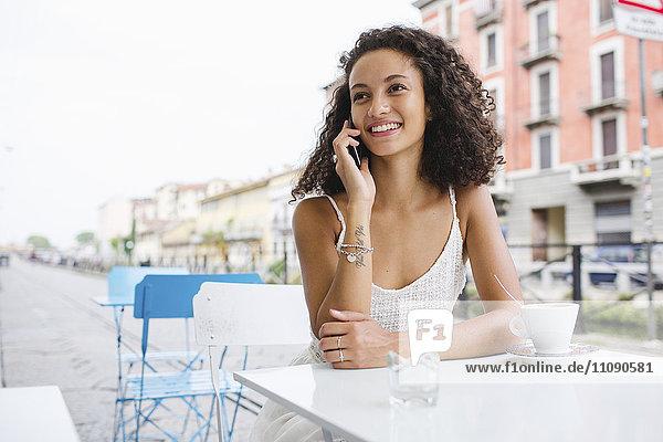 Porträt einer lächelnden jungen Frau am Telefon im Straßencafé