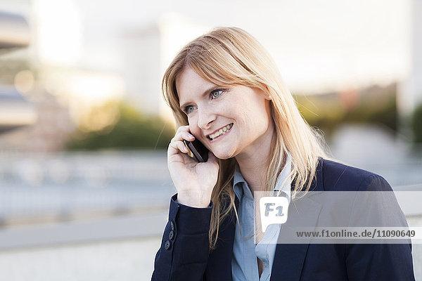 Lächelnde blonde Geschäftsfrau am Telefon