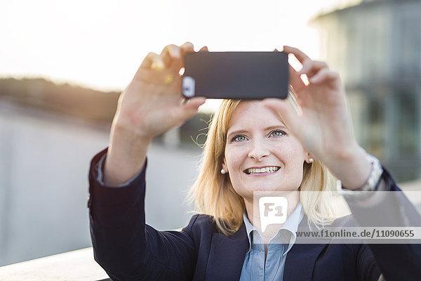 Porträt einer lächelnden  blonden Geschäftsfrau  die sich mit dem Smartphone selbstständig macht.