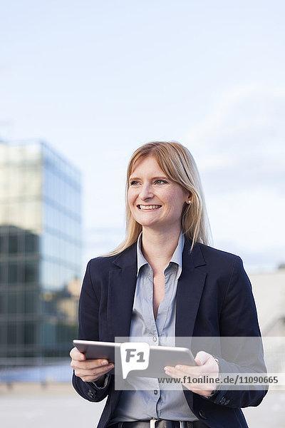Porträt einer lächelnden Geschäftsfrau mit Tablette