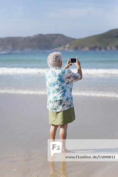 Rückansicht einer älteren Frau am Strand  die mit dem Smartphone fotografiert
