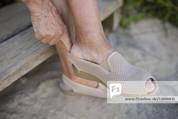 Seniorin beim Schuhanziehen