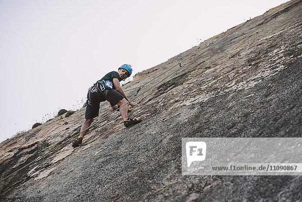 Junger Mann klettert auf eine Felswand