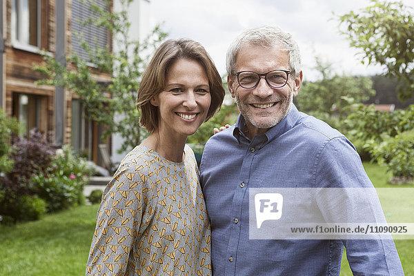 Porträt eines lächelnden reifen Paares im Garten