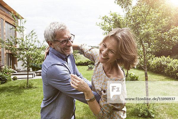 Fröhliches reifes Paar tanzt im Garten