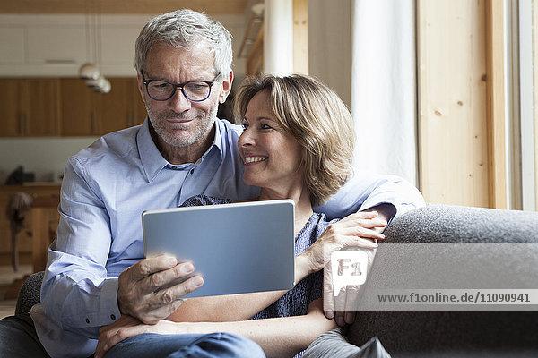 Ein reifes Paar teilt sich ein digitales Tablett auf der Couch.