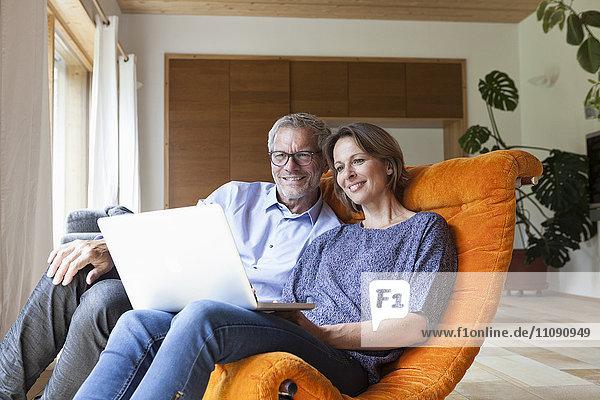 Reife Paare  die sich zu Hause einen Laptop teilen