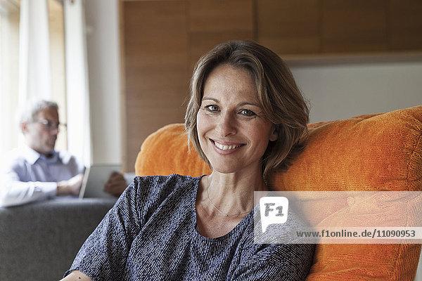 Lächelnde Frau entspannt im Sessel mit Mann im Hintergrund