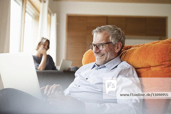 Lächelnder Mann mit Laptop im Sessel mit Frau im Hintergrund