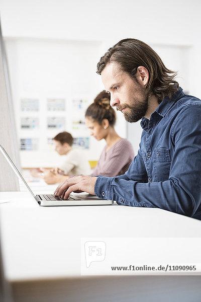 Kollegen im Büro arbeiten am Laptop