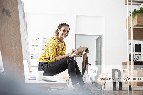Lächelnde Frau auf dem Schreibtisch sitzend mit digitalem Tablett