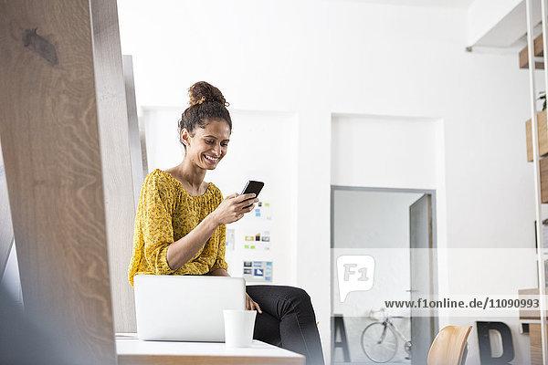 Lächelnde Frau auf dem Schreibtisch sitzend mit dem Handy