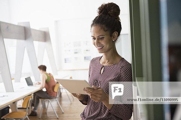 Lächelnde Frau im Büro Schreibtisch mit digitalem Tablett