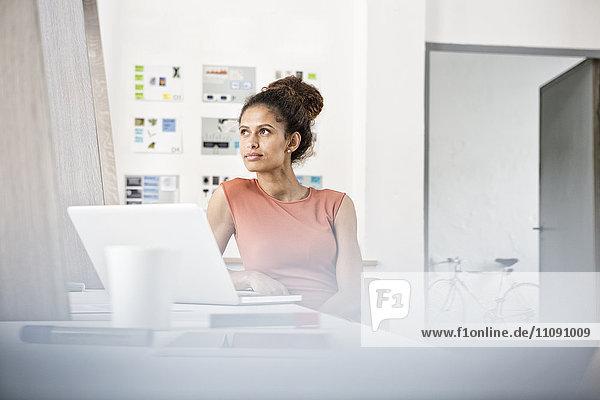 Frau sitzt am Schreibtisch und denkt nach