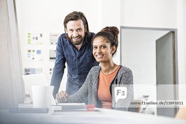 Porträt von zwei lächelnden Kollegen am Schreibtisch