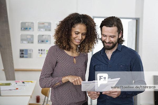 Zwei Kollegen diskutieren im Büro über Papiere