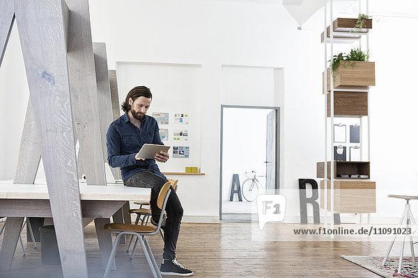 Mann auf dem Schreibtisch sitzend mit digitalem Tablett