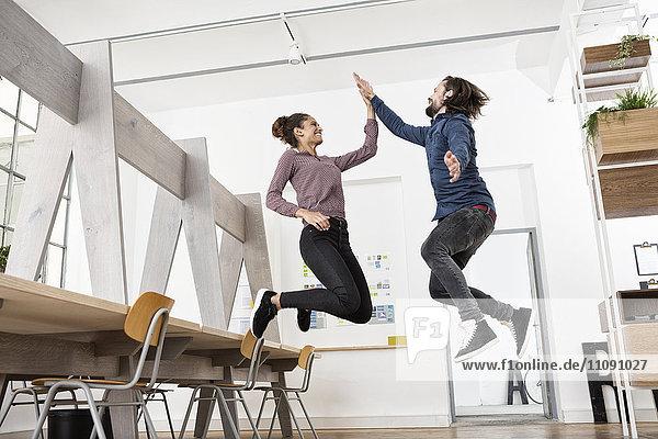 Zwei glückliche Kollegen im Büro Springen und High Fiving