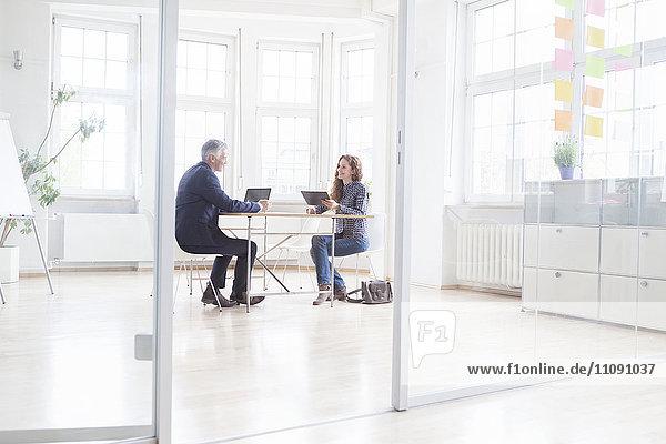 Geschäftsmann und Frau mit Laptop und Tablett im hellen Büro