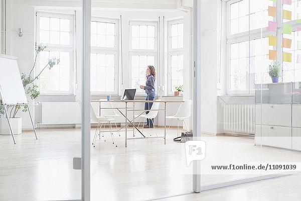 Frau am Fenster stehend in hellem Büro