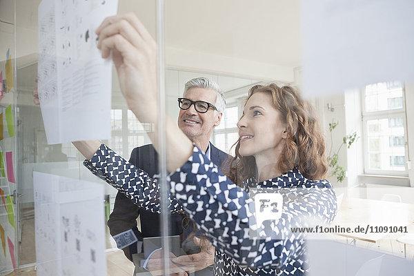 Geschäftsmann und Frau betrachten Papier auf Glasscheibe