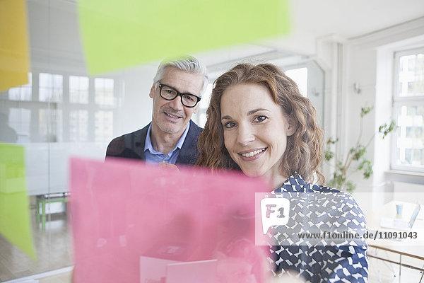 Geschäftsmann und Frau beim Betrachten von Haftnotizen an der Glasscheibe