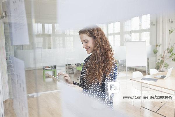 Frau im Büro mit digitalem Tablett hinter der Glasscheibe