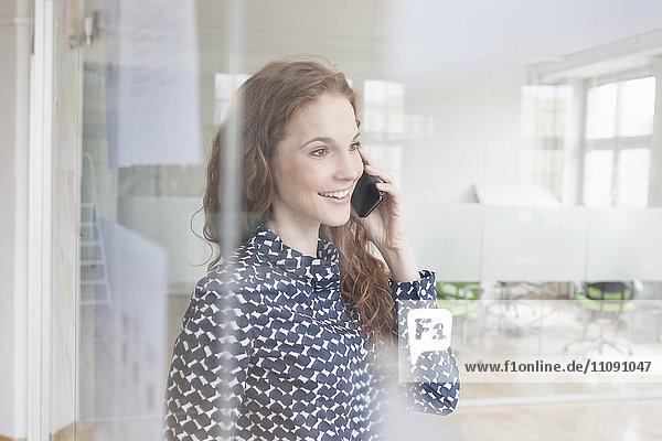 Frau im Büro am Handy