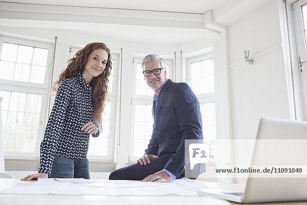 Geschäftsmann und Frau am Schreibtisch mit Plänen und Laptop