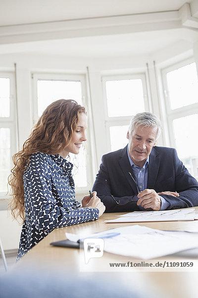 Geschäftsmann und Frau am Schreibtisch besprechen Pläne