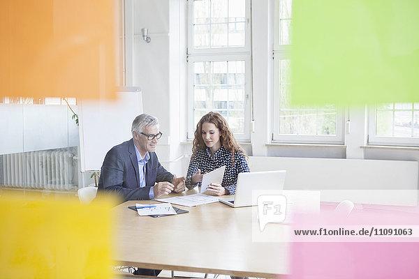 Geschäftsmann und Frau am Schreibtisch mit Tablette