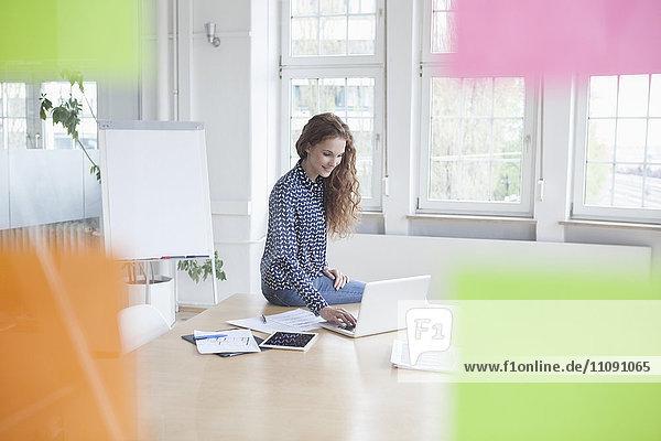 Frau mit Laptop im Sitzungssaal