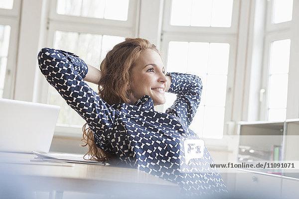 Lächelnde Frau am Schreibtisch im Büro