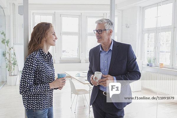 Geschäftsmann und Frau im Büro beim Kaffeetrinken