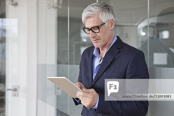 Reifer Geschäftsmann mit Tablette